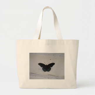 A borboleta preta e azul no branco lavou a madeira bolsa para compras