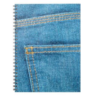 A calças de ganga suporta o caderno de bolso
