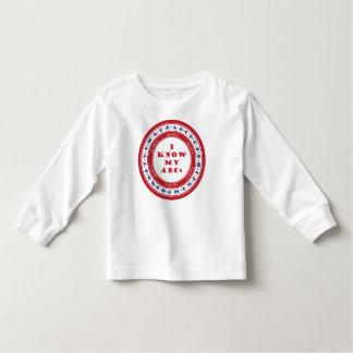 A criança aprende o t-shirt do alfabeto
