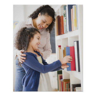 A filha de ajuda da mãe escolhe o livro na pratele poster