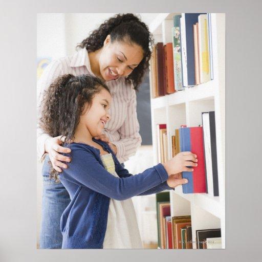 A filha de ajuda da mãe escolhe o livro na pratele posters