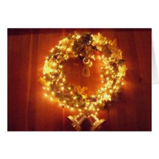 A grinalda do Feliz Natal ilumina o cartão do sino