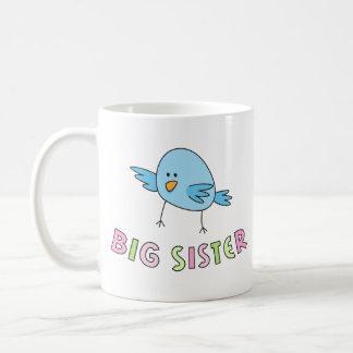 A irmã mais velha caçoa a caneca pássaro bonito e