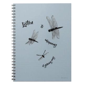 A libélula mostra em silhueta o caderno espiral