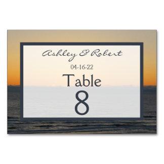 A mesa do por do sol do casamento numera cartões