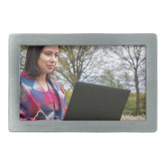 A mulher senta-se com o laptop no prado de