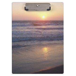 A praia do oceano acena a prancheta do por do sol