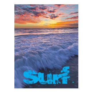 A praia surfando acena no por do sol cartão postal
