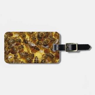 Abelhas do mel na colmeia com a rainha no meio tag de mala