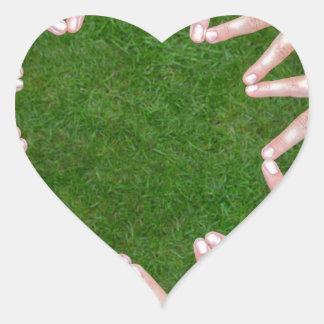 Adesivo Coração Muitos braços das crianças com as mãos que fazem a