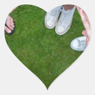 Adesivo Coração Muitos braços das crianças com as mãos que fazem o