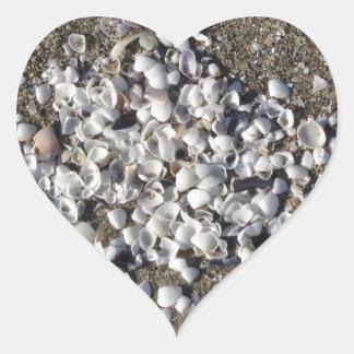 Adesivo Coração Seashells na areia. Fundo da praia do verão