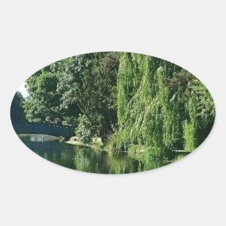 Adesivo Oval Caminhada ensolarada verde do rio das árvores do