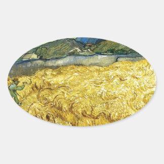 Adesivo Oval Campos de trigo com a ceifeira no nascer do sol -