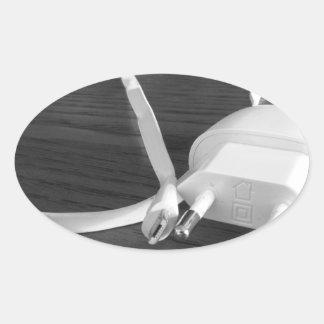 Adesivo Oval Carregador branco do smartphone na mesa de madeira