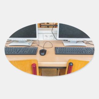 Adesivo Oval Dois computadores na sala de aula no segundo grau