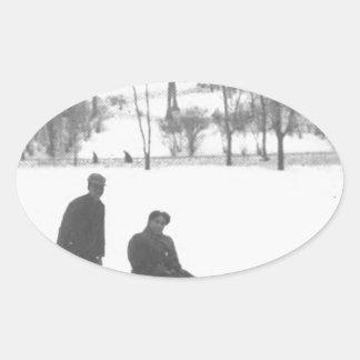 Adesivo Oval Dois meninos que puxam duas meninas em trenós