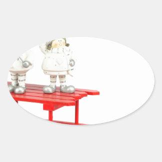 Adesivo Oval Estatuetas do Natal das crianças no trenó vermelho