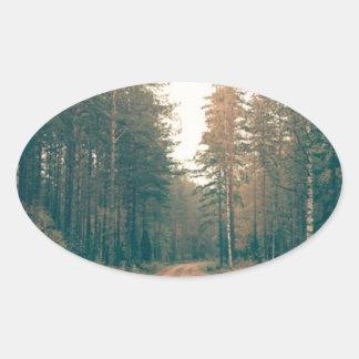 Adesivo Oval Estrada de terra de Brown entre o dia com folhas