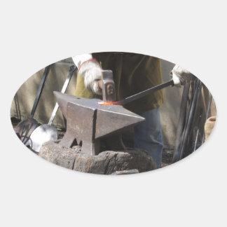 Adesivo Oval Ferreiro que forja manualmente o metal derretido