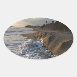 Adesivo Oval Fotografia das ondas que batem a areia