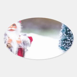 Adesivo Oval Modelo de Papai Noel que está na neve branca