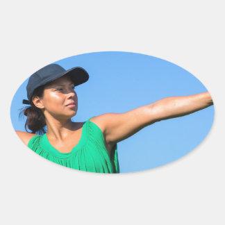 Adesivo Oval Mulher com da luva e do boné basebol de jogo fora