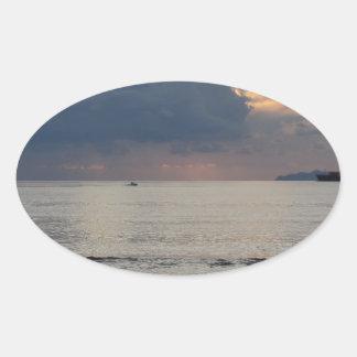 Adesivo Oval Por do sol morno do mar com navio de carga e um