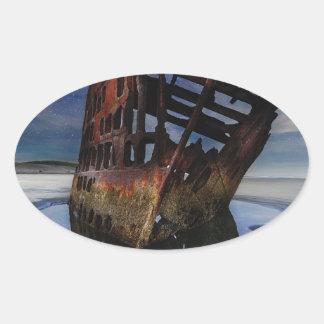 Adesivo Oval Shipwreck de Peter Iredale sob o céu nocturno