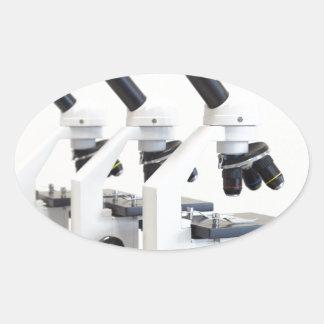 Adesivo Oval Três microscópios em seguido isolados no fundo