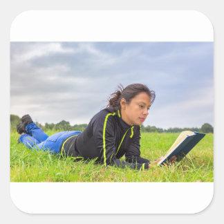 Adesivo Quadrado Jovem mulher que encontra-se no livro de leitura