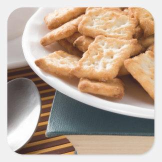 Adesivo Quadrado Placa branca com os biscoitos no livro velho