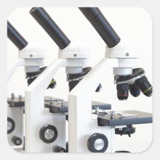 Adesivo Quadrado Três microscópios em seguido isolados no fundo