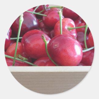 Adesivo Redondo Beira de cerejas frescas no fundo de madeira