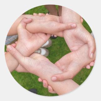 Adesivo Redondo Braços com mãos das meninas que guardaram-se