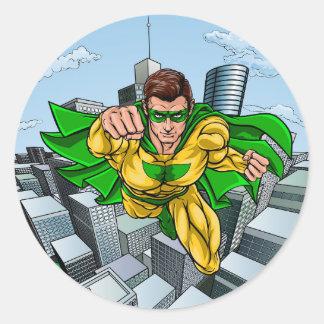 Adesivo Redondo Cidade do super-herói do vôo da banda desenhada