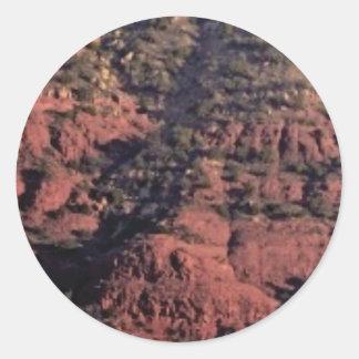 Adesivo Redondo colisões e protuberâncias na rocha vermelha