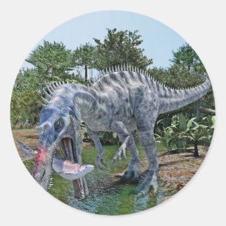 Adesivo Redondo Dinossauro de Suchomimus que come um tubarão em um