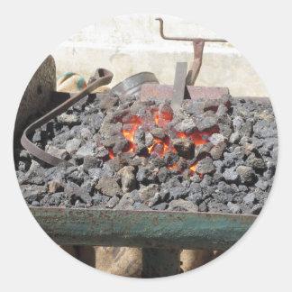 Adesivo Redondo Fornalha antiquado do ferreiro. Carvões ardentes