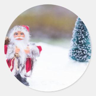 Adesivo Redondo Modelo de Papai Noel que está na neve branca
