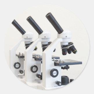 Adesivo Redondo Três microscópios em seguido isolados no fundo