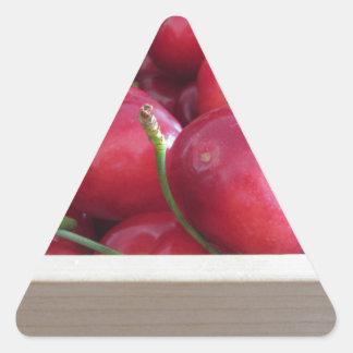 Adesivo Triangular Beira de cerejas frescas no fundo de madeira