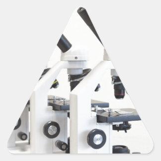 Adesivo Triangular Três microscópios em seguido isolados no fundo