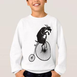 Agasalho Cabra que monta uma bicicleta do Farthing da moeda