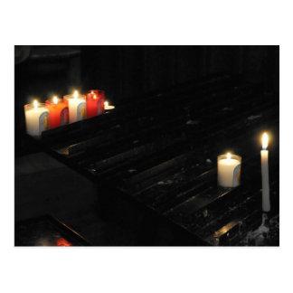 Algumas velas religiosas em um apoio preto em um cartão postal