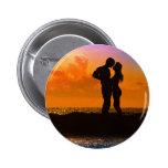 Amantes que beijam no por do sol na praia botons