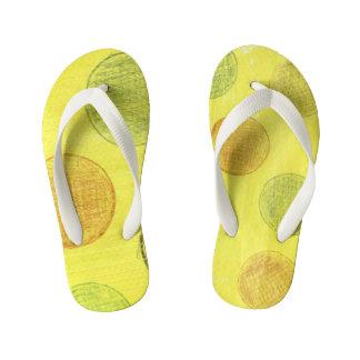 Amarelo das sandálias das crianças com pontos de
