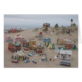Areia, mar, e cartão de Natal da vila da neve