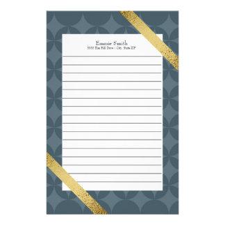 Artigos de papelaria azuis escuro e ouro alinhados