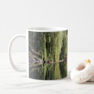 Árvores de salgueiro refletidas no rio caneca de café